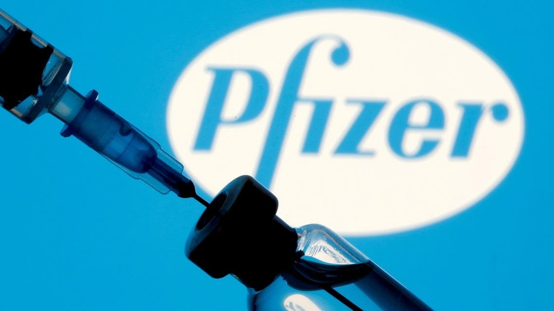 A vial and syringe are seen in front of a displayed Pfizer logo in this illustration. (Reuters)
