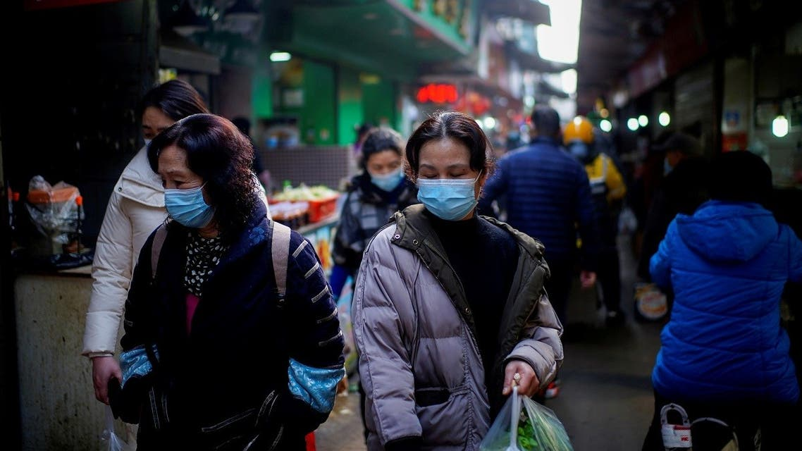 People wearing face masks walk on a street market, following an outbreak of the coronavirus in Wuhan, Hubei province, China, on February 8, 2021. (Reuters)