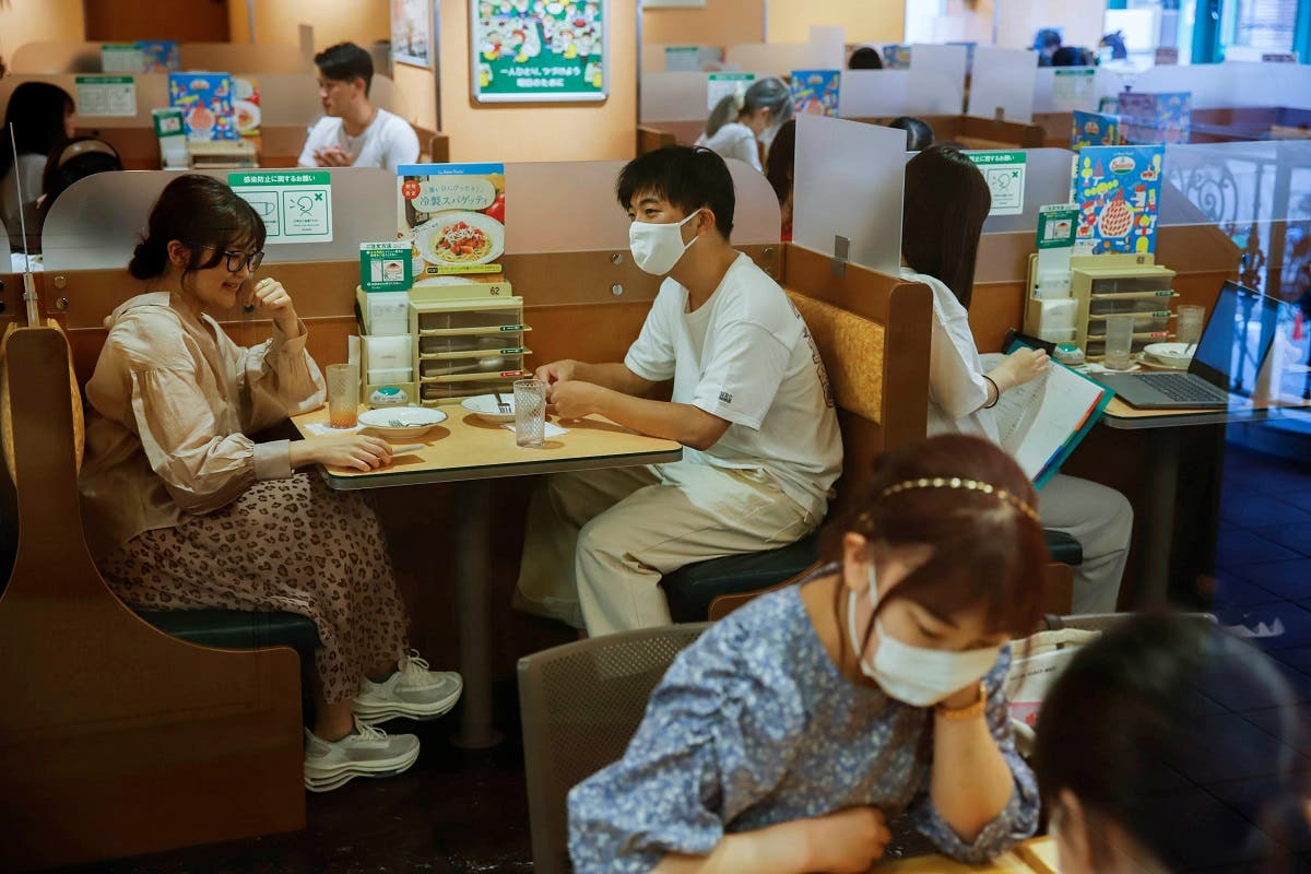 People sit in a restaurant using plexiglass separators to protect customers from coronavirus  in the Shibuya area of Tokyo, Japan, July 29, 2021.  (Reuters)