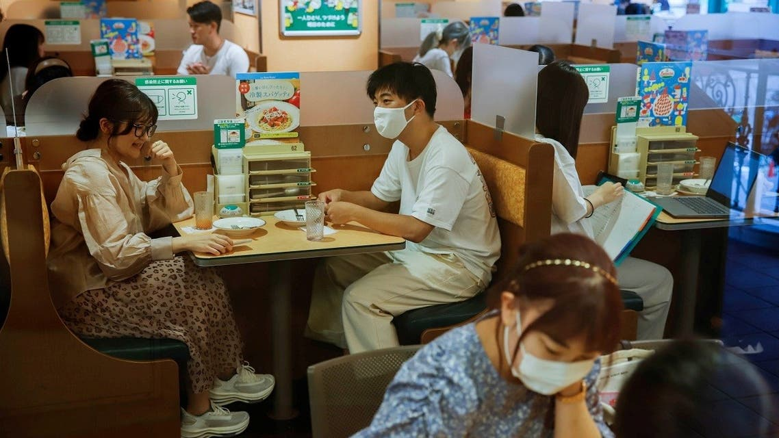 People sit in a restaurant using plexiglass separators to protect customers from coronavirus (COVID-19) disease in the Shibuya area of Tokyo, Japan, July 29, 2021.  (Reuters)