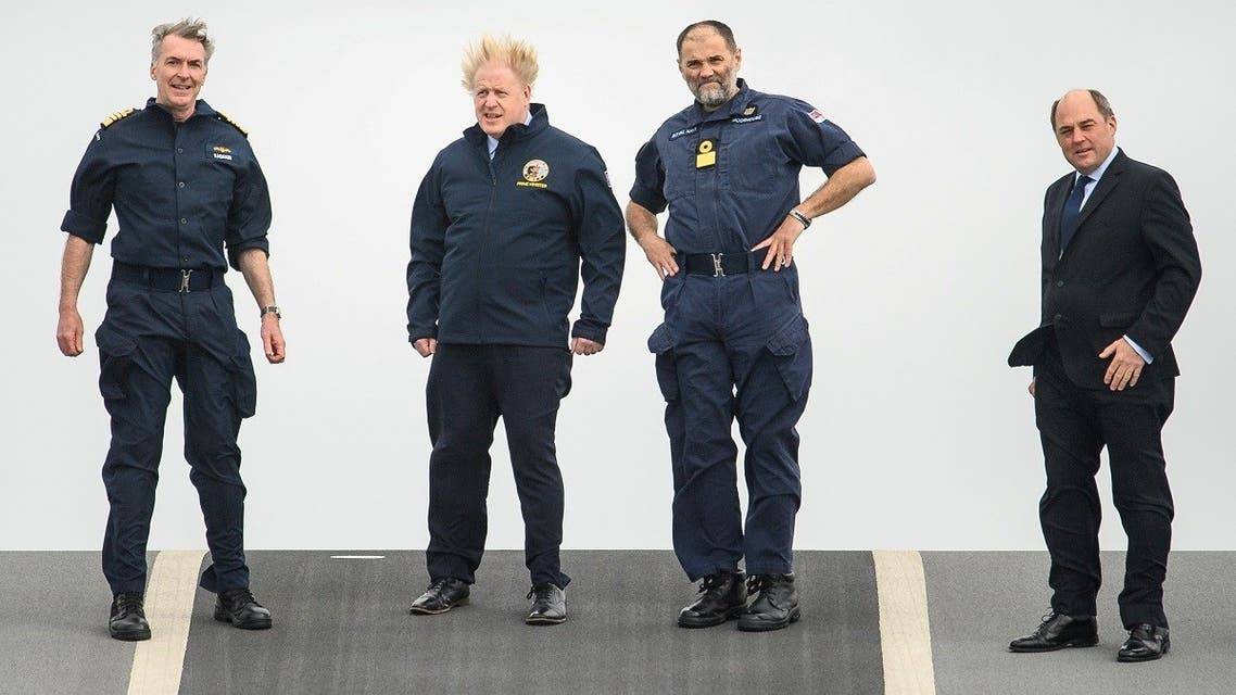 Prime Minister Boris Johnson, First Sea Lord Admiral Tony Radakin, Commodore Steve Moorhouse and Defence Secretary Ben Wallace face strong winds as they walk on the flight deck during a visit to HMS Queen Elizabeth aircraft carrier in Portsmouth, Britain, on May 21, 2021. (Reuters)