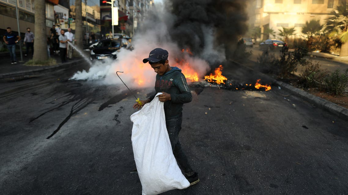 A Lebanese boy collects items from the street near tires set on fire during a protest at a main road in Lebanon's capital Beirut against dire living conditions amidst the ongoing economical and political crisis, on June 28, 2021. (File photo: AFP)
