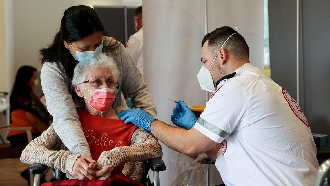 An elderly woman receives a booster shot of her vaccination against the coronavirus disease (COVID-19) at an assisted living facility, in Netanya, Israel January 19, 2021.  (Reuters)