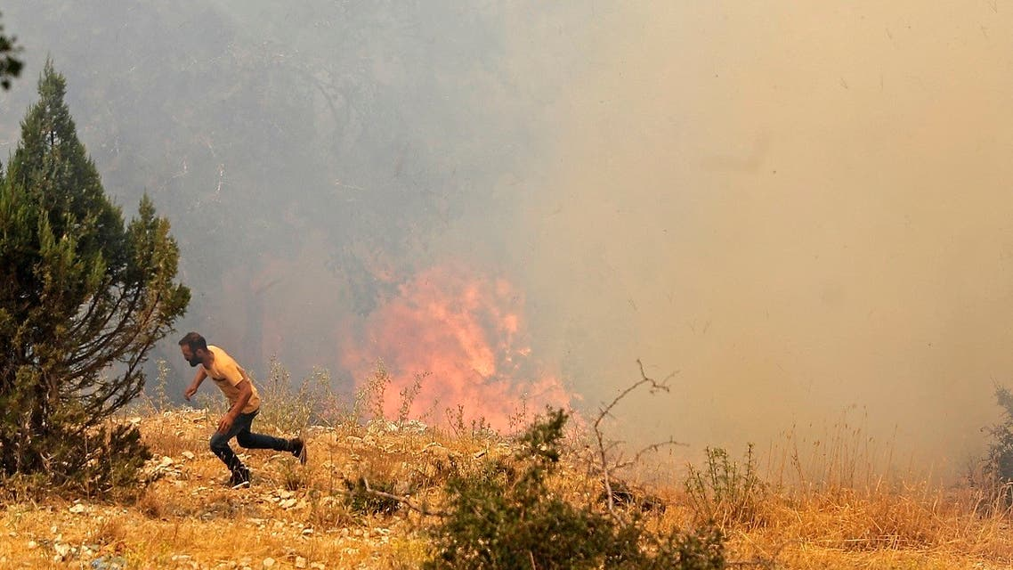 A man runs for cover as Lebanese firemen douse the flames in the forests of the Qoubaiyat area in northern Lebanon's Akkar, July 29, 2021. (AFP)