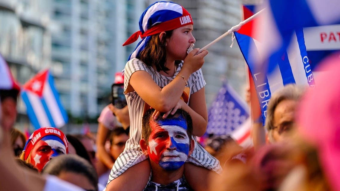 A girl sits on the shoulder of a man in reaction to reports of protests in Cuba against its deteriorating economy, in Miami, July 17, 2021. (Reuters)