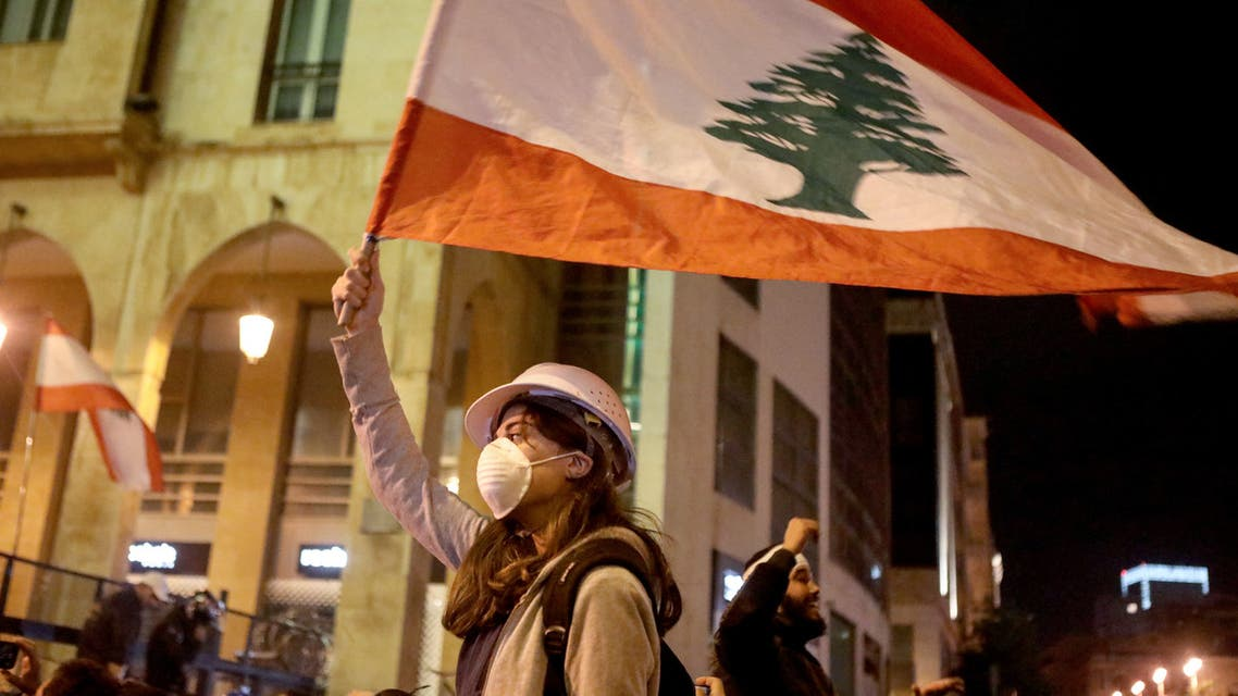 Lebanese protestors wave flags and shout anti-corruption slogans outside the parliament during a protest in Beirut on Jan. 21, 2020. (Reuters)