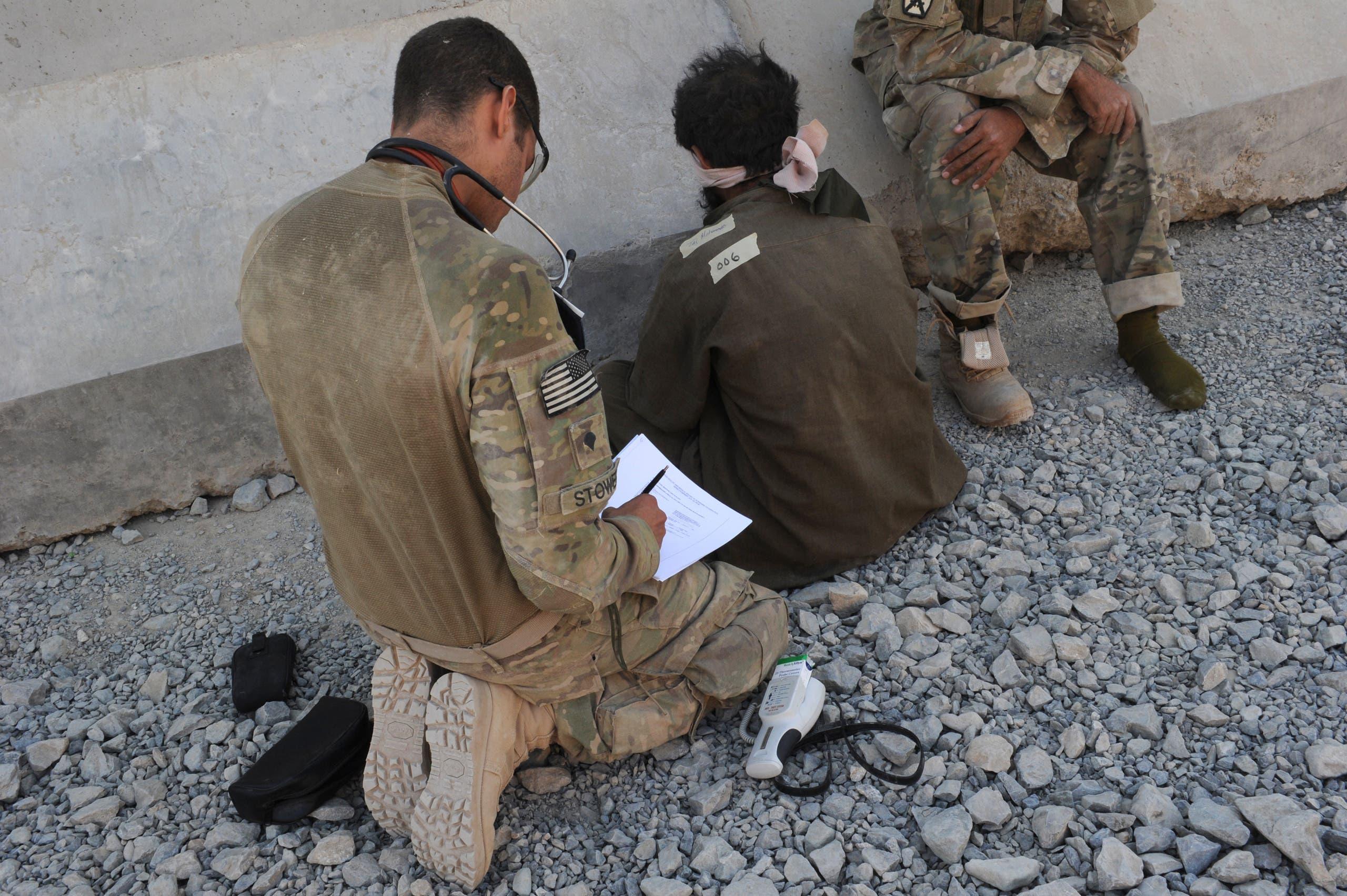 جندي أميركي يستجوب عنصرا من طالبان ومعه مترجم أفغاني في قندهار في 2011 (أرشيفية)