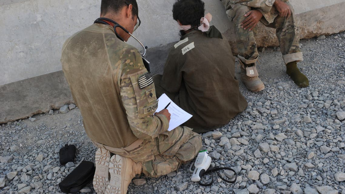 A US military medic (L) accompanied by an interpreter (R) examines a captured Taliban suspect (C) waiting interrogation at the Forward Operating Base Pasab in Zahri district, Kandahar province southern Afghanistan on August 15, 2011 following their capture during a five hour ground and air assault operation. According to Major Kirby Dennis, operations officer of Task Force 2-87, this US army operation will reduce the insurgents offensive capability following the capature of eight individuals, including two suspected Taliban leaders and assorted bomb making components. AFP PHOTO / ROMEO GACAD
