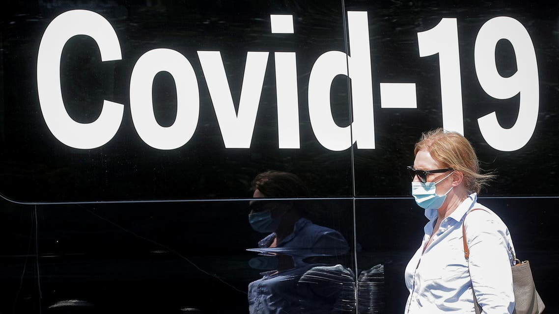 A woman wearing a mask passes by a coronavirus disease mobile testing van, as cases of the infectious Delta variant of COVID-19 continue to rise, in Washington Square Park in New York City, U.S., July 22, 2021. (Reuters)