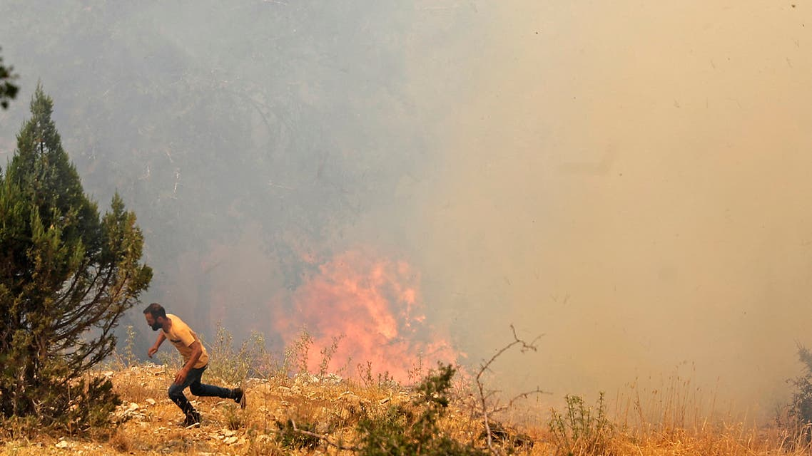 A man runs for cover as Lebanese firemen douse the flames in the forests of the Qubayyat area in northern Lebanon's remote Akkar region on July 29, 2021. (File photo: AFP)