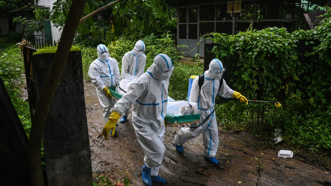 n this file photo taken on July 10, 2021 volunteers wearing personal protective equipment (PPE) carry the body of a victim of the Covid-19 coronavirus to a cemetery in Hlegu Township in Yangon. (File photo: AFP)