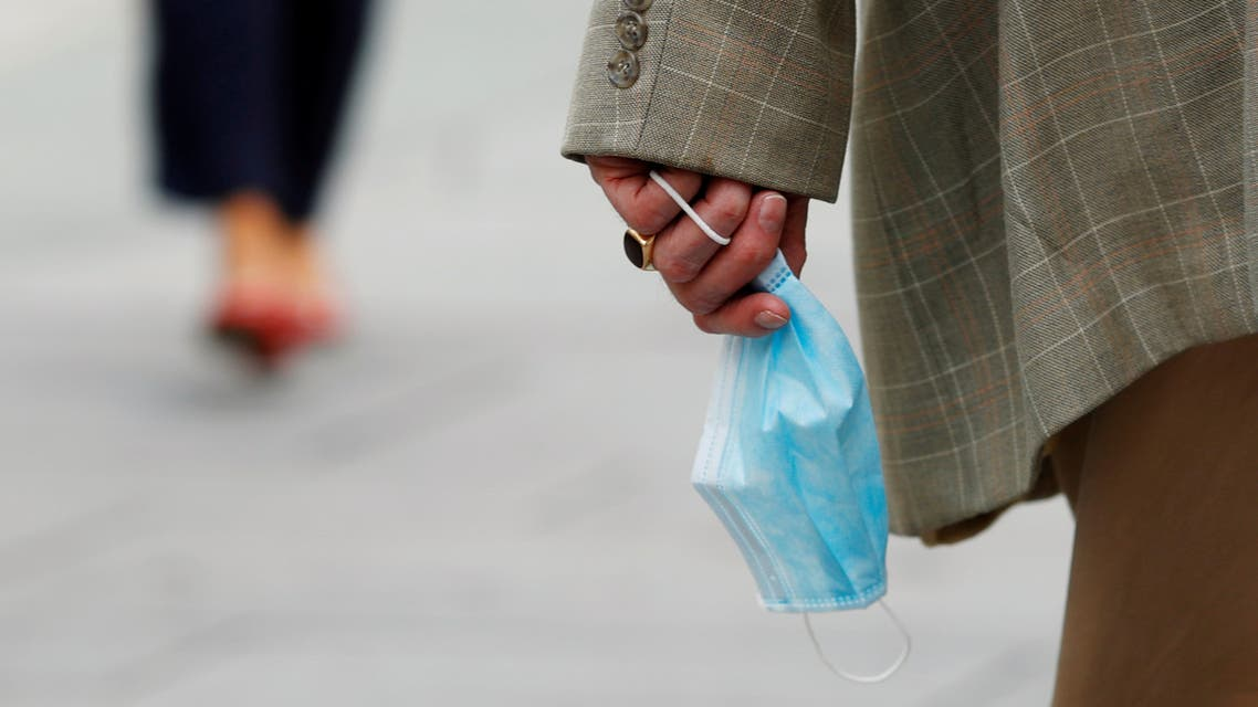 A man holds a protective mask as he walks down the street as the coronavirus disease (COVID-19) outbreak continues in Vienna, Austria September 17, 2020. (Reuters)