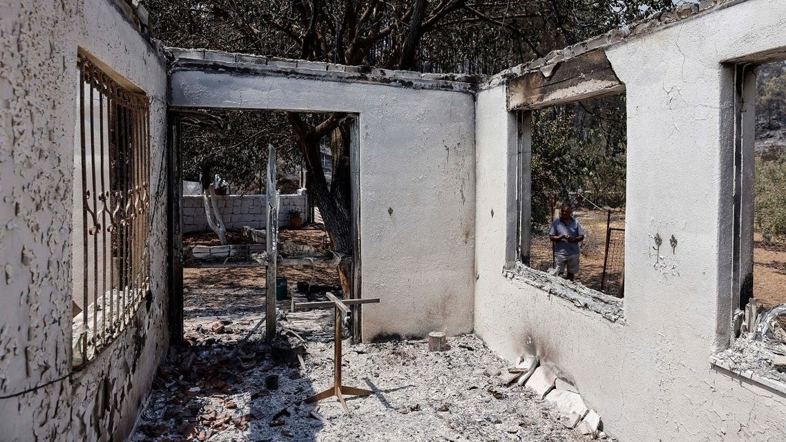 A man stands in front of his burnt house during a wildfire near Marmaris, Turkey, July 31, 2021. (Reuters/Umit Bektas)
