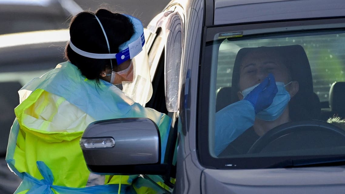 A health worker dressed in protective gear conducts COVID-19 testing at the St. Vincents Hospital drive-through testing clinic at Bondi in Sydney on July 6, 2021, as the city remains in lockdown for a second week to contain an outbreak of the highly contagious Delta Covid-19 variant.