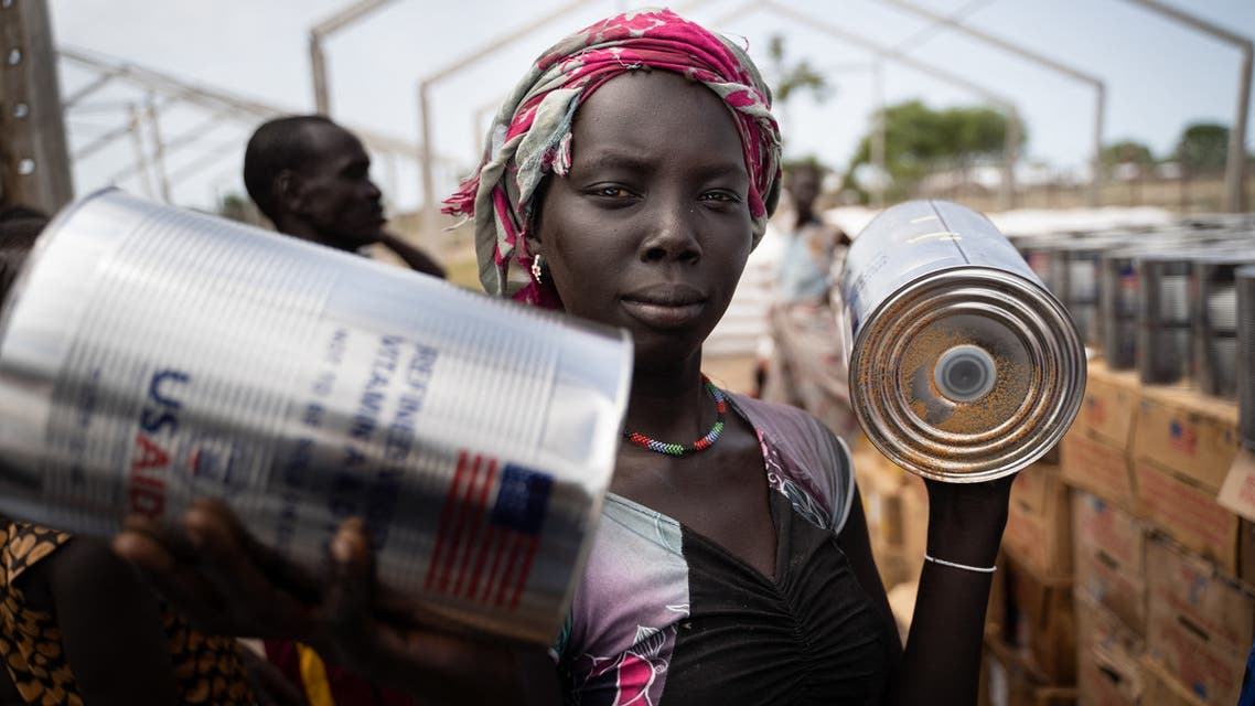 A woman from Murle ethnic group receives cans of oil during a food distribution by United Nations World Food Programme (WFP) in Gumuruk, South Sudan, on June 10, 2021, as her village where recently attacked by armed youth group. An escalation in conflict has led to the displacement of thousands of individuals in the Greater Pibor Administrative Area (GPAA, former Pibor County) in May 2021, deepening humanitarian needs in an area already facing catastrophic conditions across sectors and which had been classified as 'famine likely' by the Global Famine Review of Integrated Food security phase (IPC) in November, 2020.