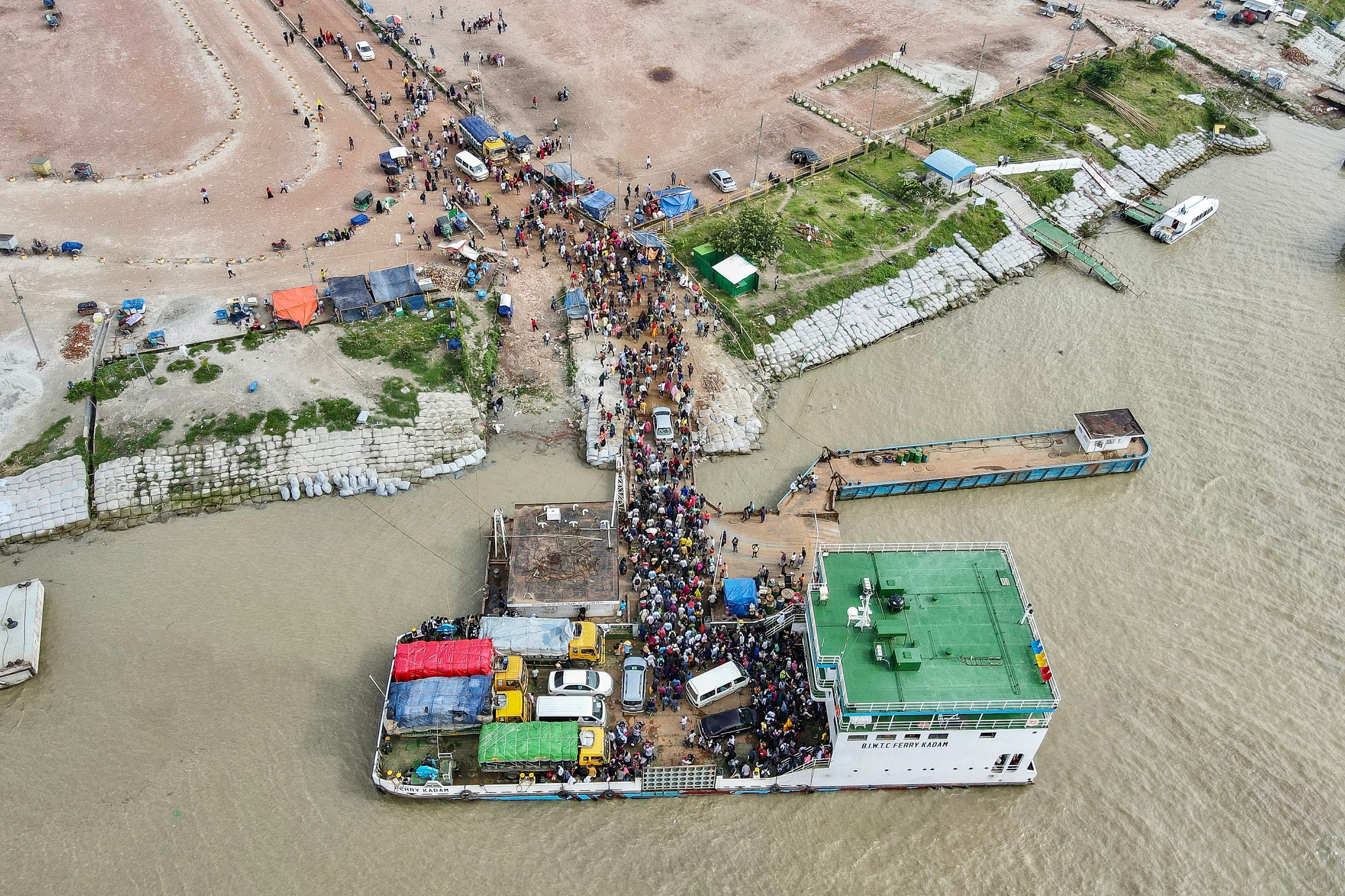 People wait to disembark from a ferry in Sreenagar on July 31, 2021 after they return to their work areas post the Bangladesh government relaxed the lockdown norms for all export oriented factories which were earlier imposed to curb the spread of COVID-19 coronavirus. (AFP)