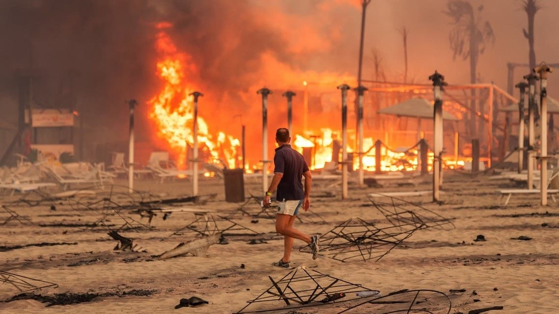 A man walks in front of a fire at Le Capannine beach in Catania, Sicily, Italy, July 30, 2021, in this photo obtained from social media on July 31, 2021.( Roberto Viglianisi/via Reuters)