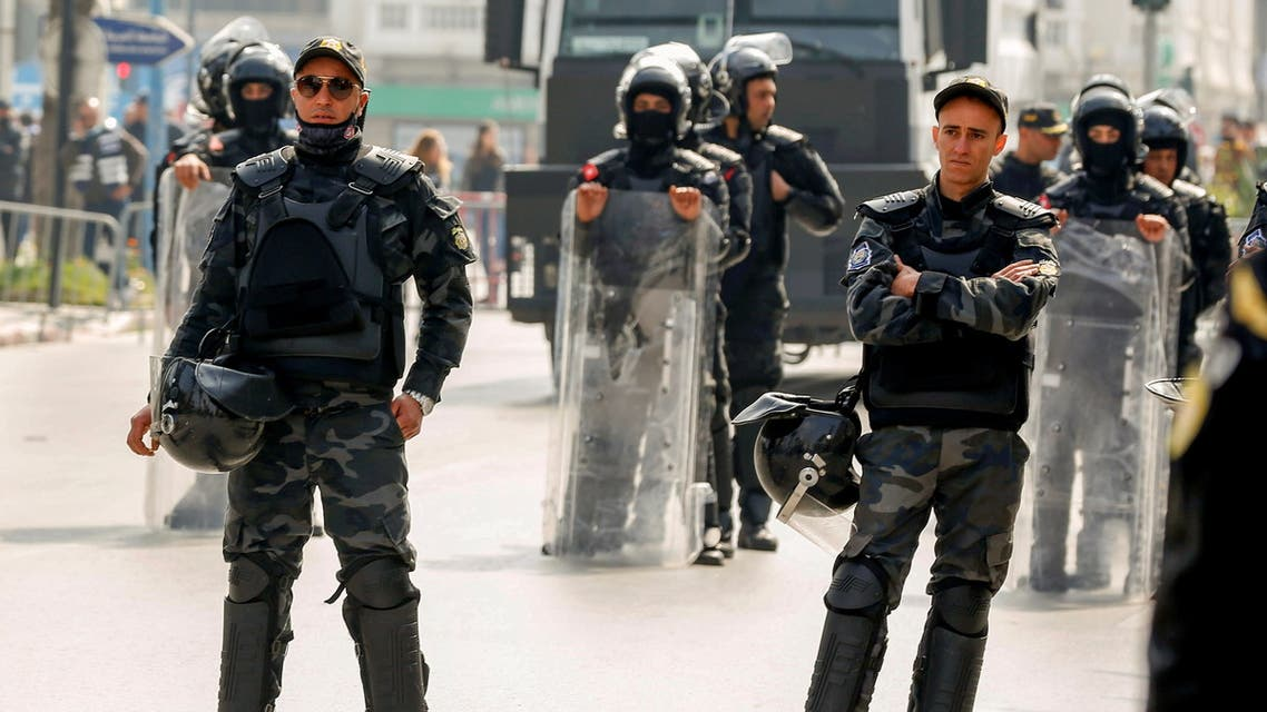 Members of security forces keep watch as supporters of Tunisia's biggest political party, the moderate Islamist Ennahda, march during a rally in opposition to President Kais Saied, in Tunis, Tunisia February 27, 2021. (Reuters)