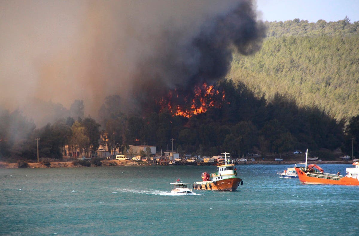 Smoke rises from a forest fire, threatening a residential area in the Aegean coastal town of Bodrum, Turkey, Thursday, July 29, 2021. (IHA via AP)
