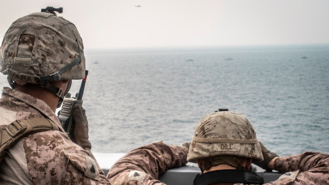 Marines onboard the amphibious transport dock ship USS John P. Murtha (LPD 26) watch nearby Iranian fast inland attack craft, as it transits the Strait of Hormuz, off Oman, in this undated handout picture released by U.S. Navy on August 12, 2019. (File photo: Reuters)