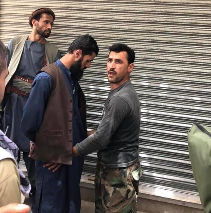 سرباز افغان در حال بررسی جنگجوی طالبان پس از بازداشت وی