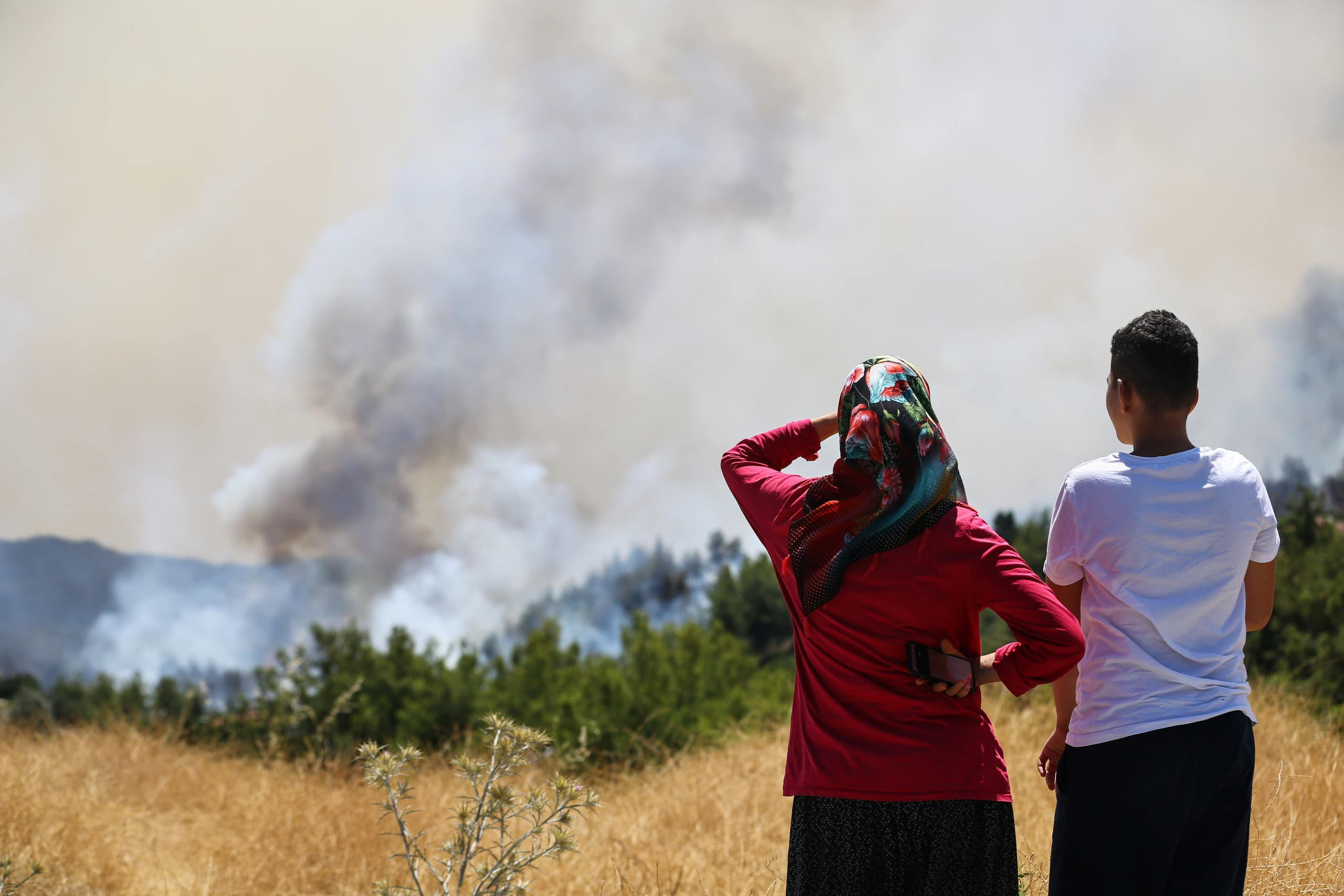 Locals watch a wildfire near the town of Manavgat, east of the resort city of Antalya, Turkey, July 31, 2021. (Reuters)