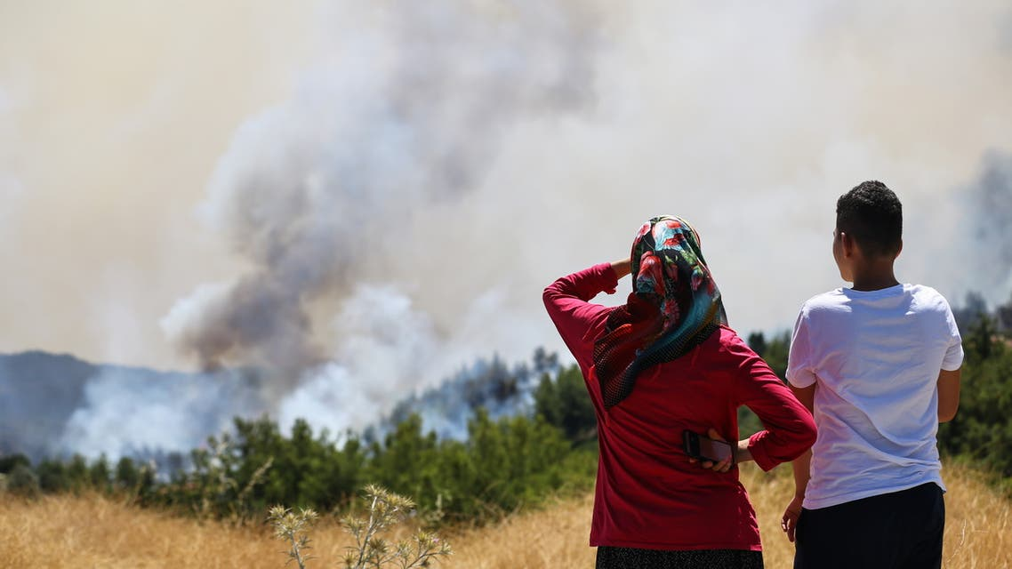 Locals watch a wildfire near the town of Manavgat, east of the resort city of Antalya, Turkey, July 31, 2021. REUTERS/Kaan Soyturk