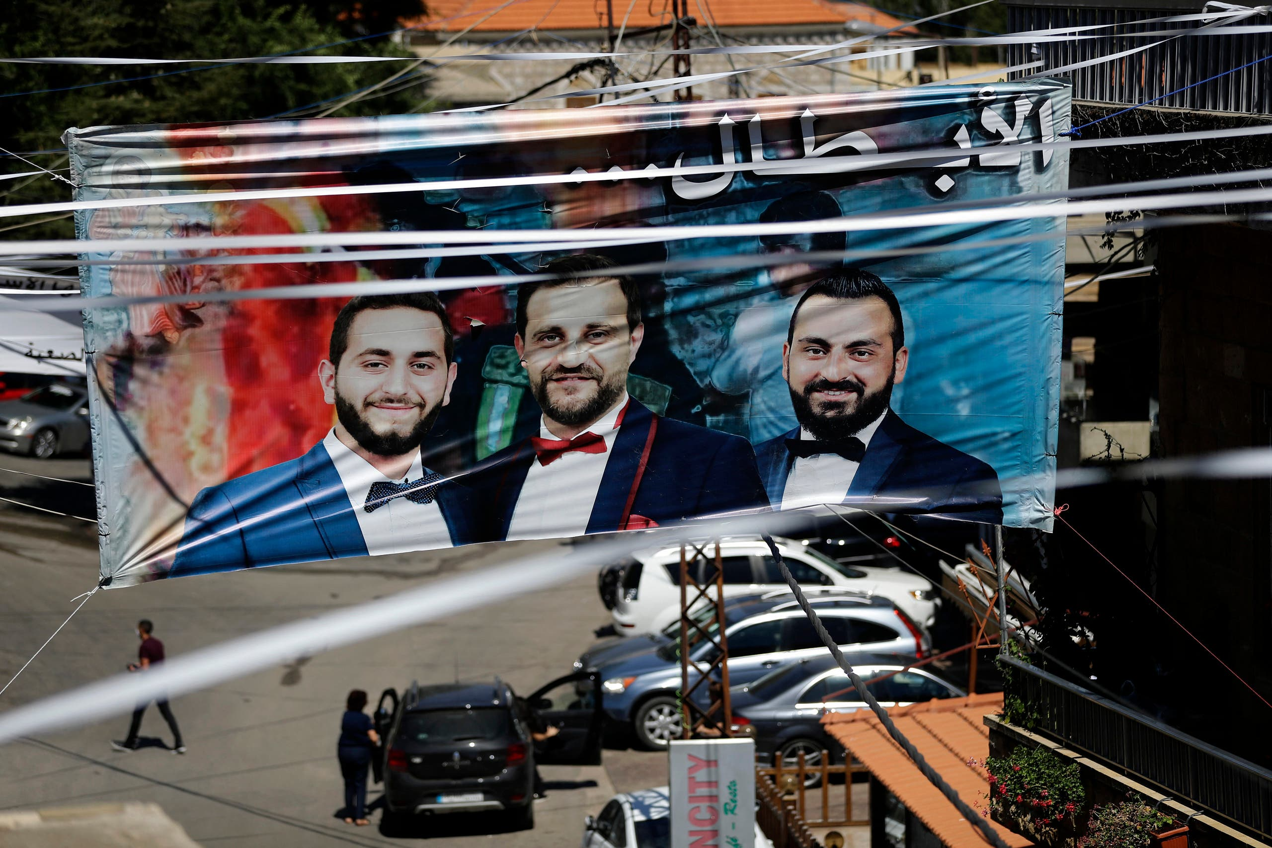 A banner bearing the portraits of firefighters Charbel Hitti, Charbel Karam, and Najib Hitti is seen hanging during their funeral procession in their hometown of Qartaba, north of the Lebanese capital Beirut, on August 17, 2020. (AFP)