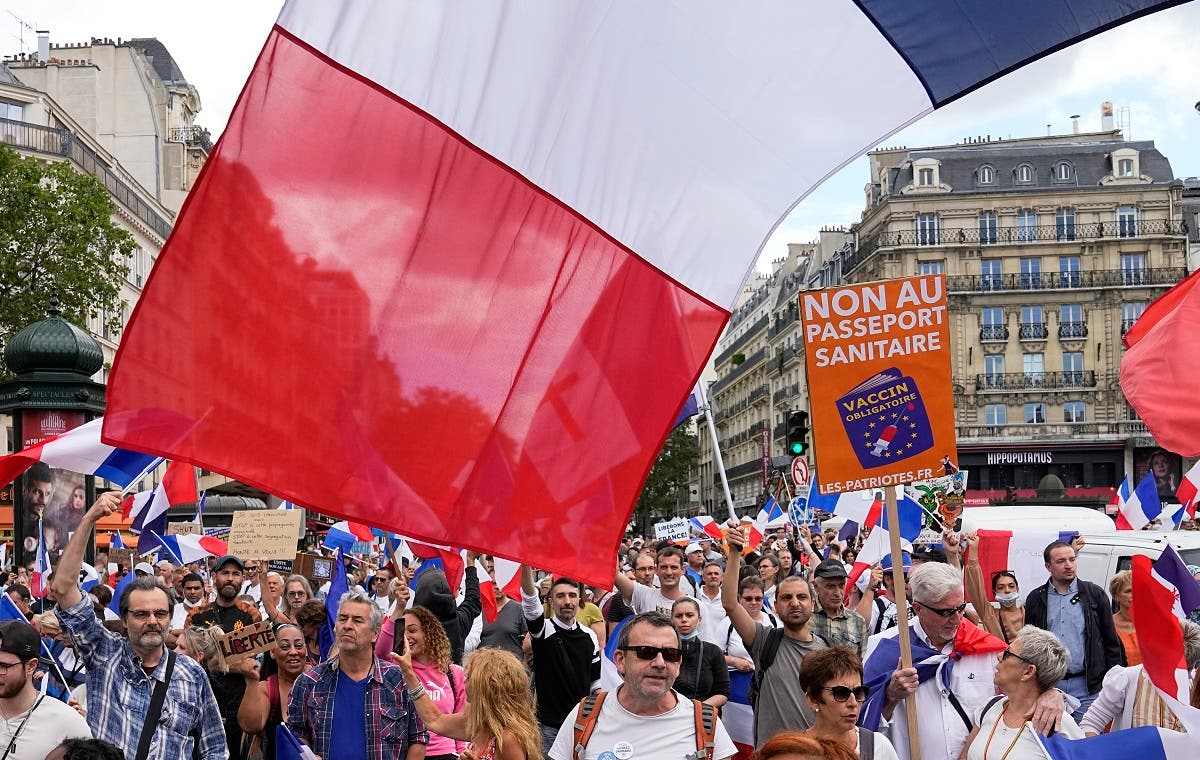 """Protestors hold signs which read in French, """"freedom"""" and """"no to the vaccine passport"""" as they attend a demonstration in Paris, France, on July 31, 2021. (AP)"""