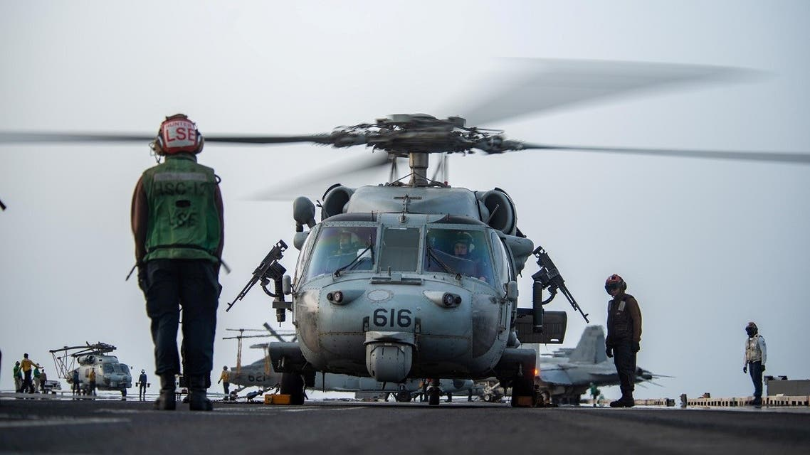 Sailors prepare an MH-60S Sea Hawk helicopter to launch on the flight deck of aircraft carrier USS Ronald Reagan (CVN 76), in response to a call for assistance from the Mercer Street. (Reuters)