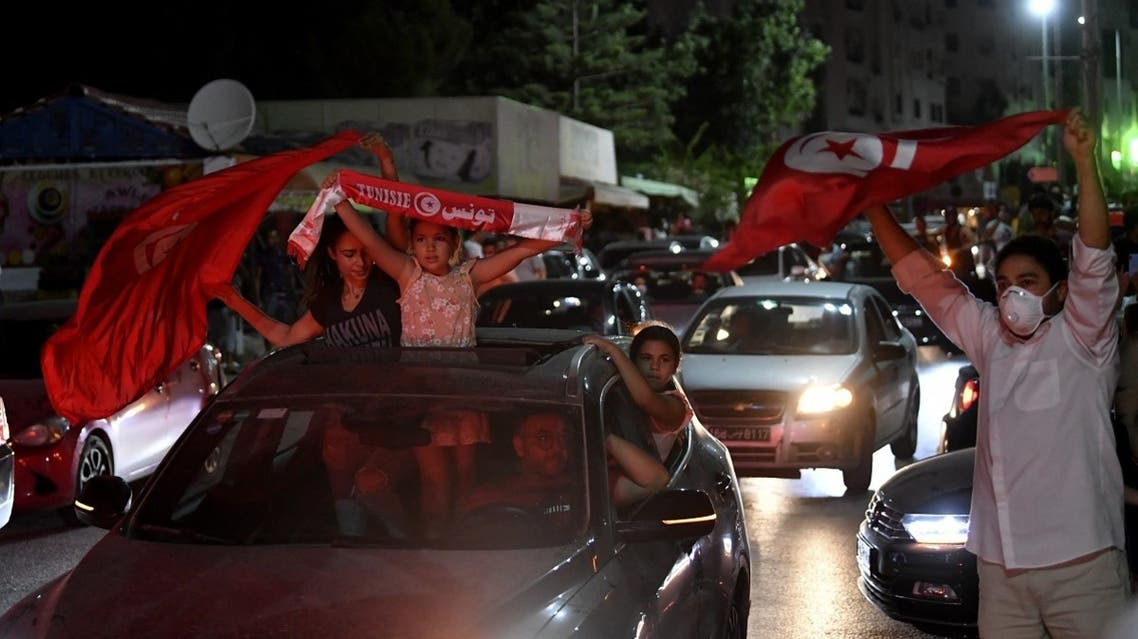 People celebrate in the streets of Tunis after Tunisian President Kais Saied announced the suspension of parliament and the dismissal of the PM, July 25, 2021. (AFP)