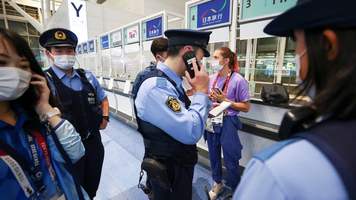 Belarusian athlete Krystsina Tsimanouskaya stands surrounded by police officers at Haneda international airport in Tokyo, Japan August 1, 2021. (Reuters)