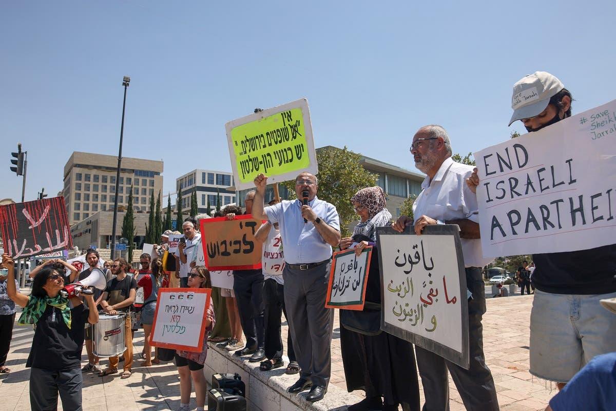 Arab Israeli Knesset member Ahmad al-Tibi (C) speaks as fellow MP Oussama al-Saadi lifts a banner, alongside Palestinian, Israeli, and foreign activists, during a demonstration outside the Supreme Court in Jerusalem, on August 2, 2021. (Ahmad Gharabli/AFP)