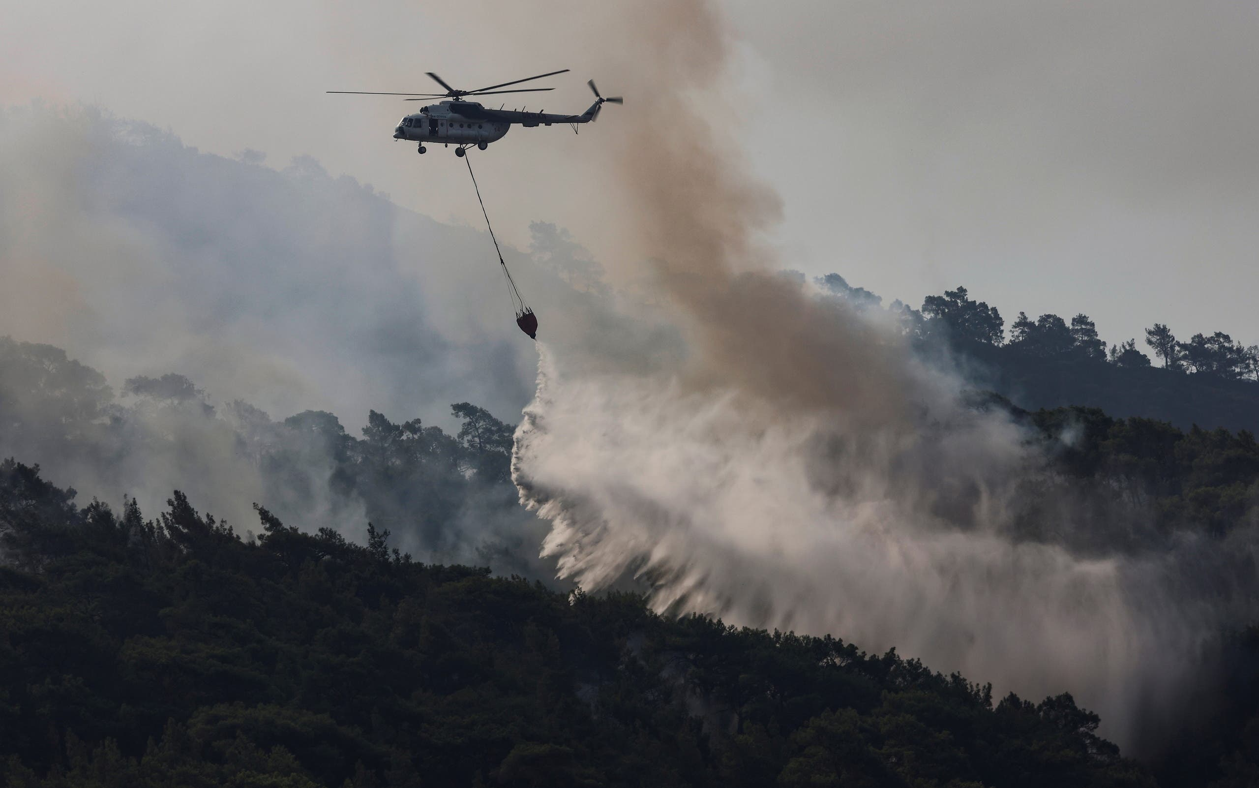 A firefighting helicopter drops water to a wildfire near Marmaris, Turkey, August 2, 2021. (Reuters)
