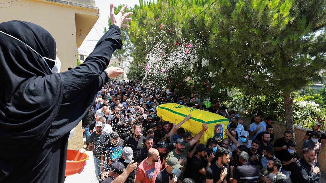 A woman throws rice as mourners carry the coffin of Hezbollah member Ali Shibli, who was killed on Saturday, during his funeral in the village of Kunin, southern Lebanon August 2, 2021. (Reuters)