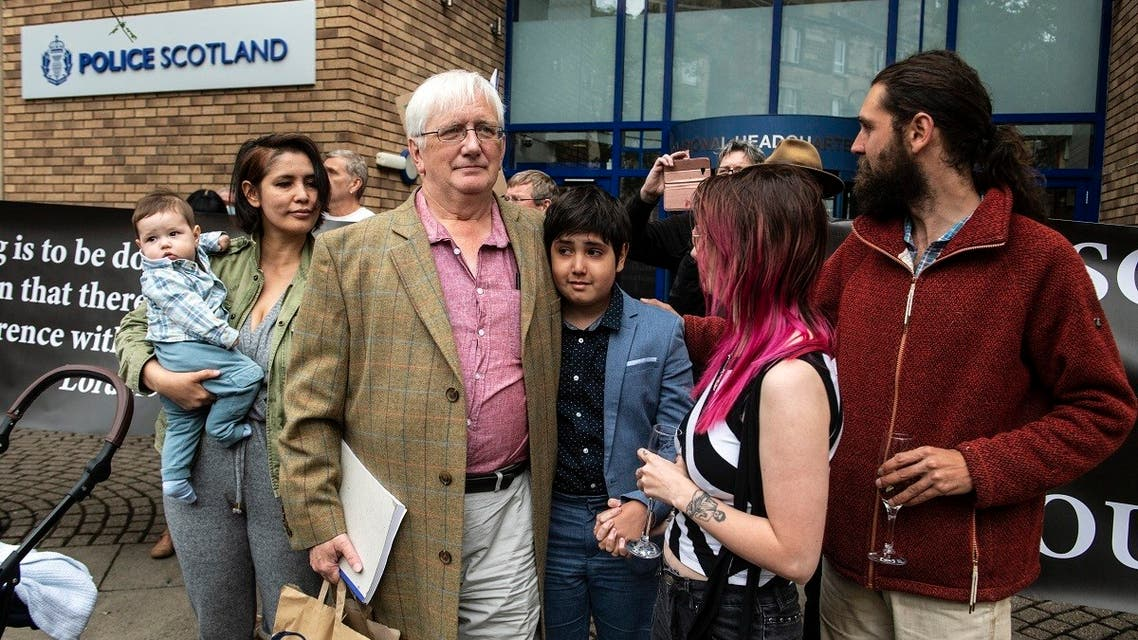 Britain's former ambassador to Uzbekistan, Craig Murray (3rd L) waits with members of his family outside St Leonard's Police Station in Edinburgh on August 1, 2021. (Andy Buchanan/AFP)