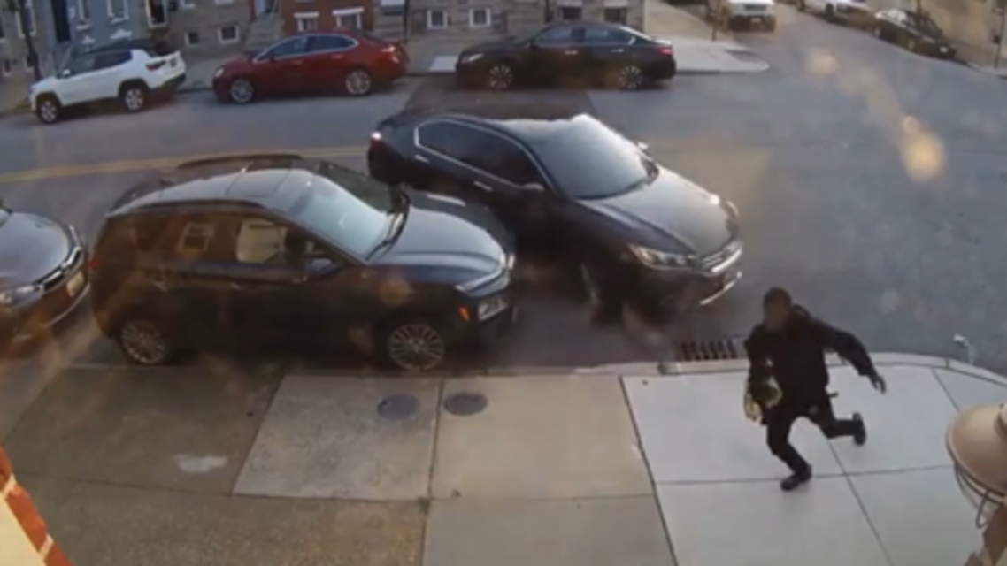 The moment a woman tries to run over a man during a heated argument in Baltimore, US. (Screengrab)