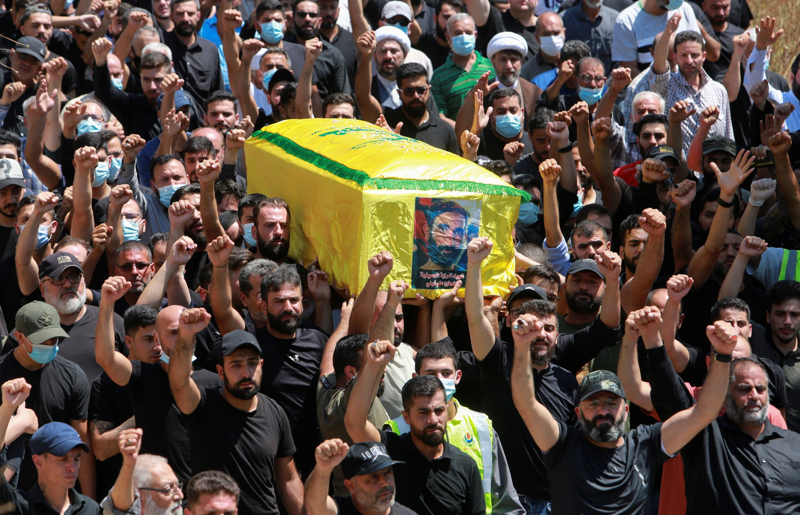 Mourners carry the coffin of Hezbollah member Ali Shibli, who was killed on Saturday, during his funeral in the village of Kunin, southern Lebanon August 2, 2021. (Reuters)