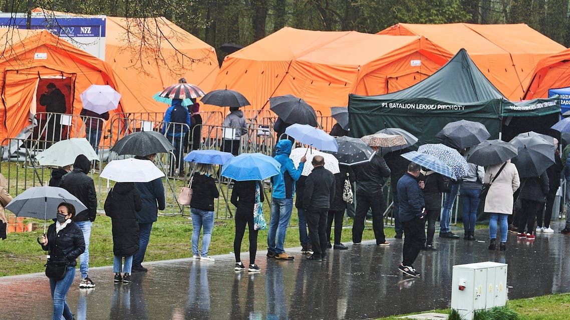 People queue in the rain at a mobile vaccination point against coronavirus disease (COVID-19) in Lodz, organised for the long weekend in several Polish cities, May 2, 2021. Tomasz Stanczak/Agencja Gazeta via REUTERS ATTENTION EDITORS - THIS IMAGE WAS PROVIDED BY A THIRD PARTY. POLAND OUT. NO COMMERCIAL OR EDITORIAL SALES IN POLAND.