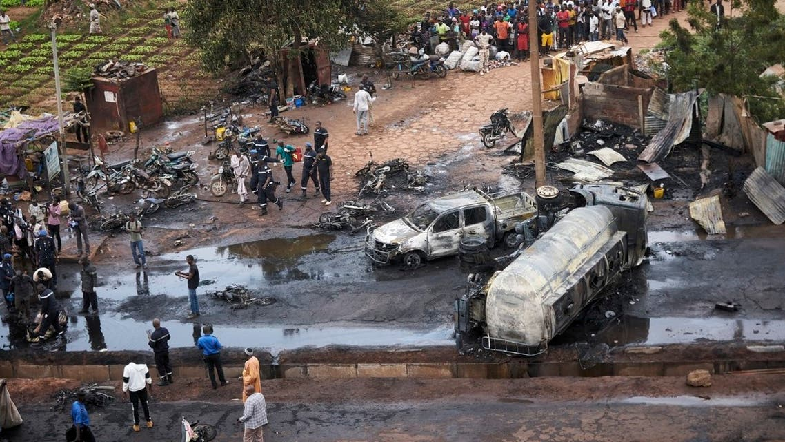 A file photo shows passers by and rescuers gather in central Bamako on September 24, 2019 at the site of car accident involving a fuel tank truck that caught fire when people tried to lift it, killing five people at least and injuring 15. (Michele cattani/AFP)