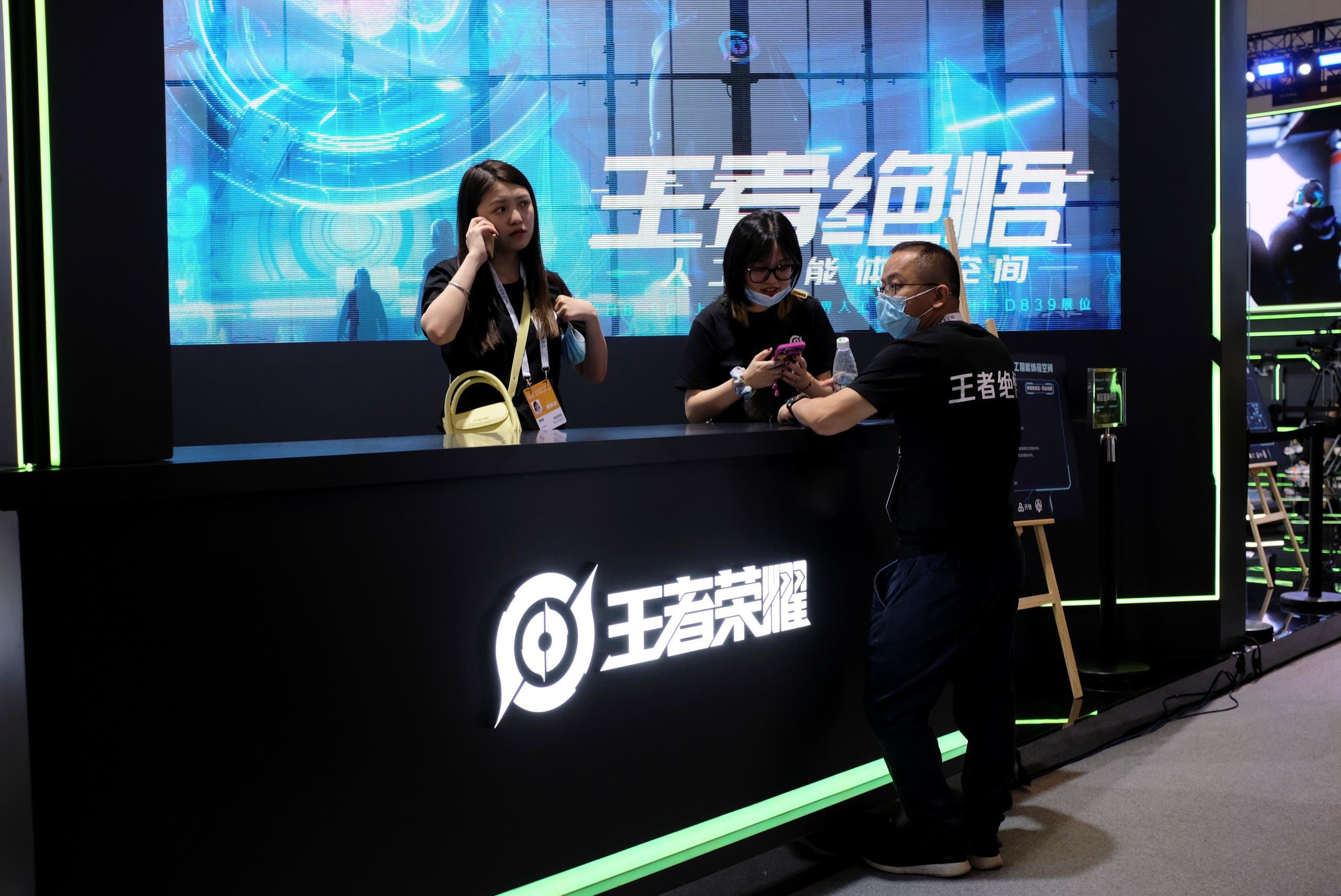 Staff members stand at the booth of Honor of Kings, a Tencent Games game, during the World Artificial Intelligence Conference (WAIC) in Shanghai, China July 8, 2021. (Reuters)