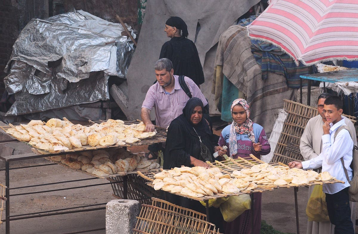 Egyptians buy bread on a street in Giza Governorate. (Reuters)