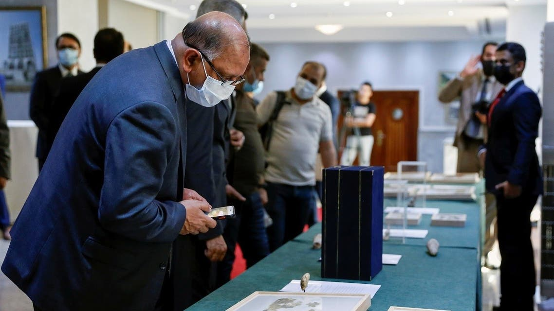 Officials look at artifacts seized by the US government and returned to Iraq, which are on display at the Ministry of Foreign Affairs in Baghdad, Iraq August 3,2021. (Reuters/Saba Kareem)
