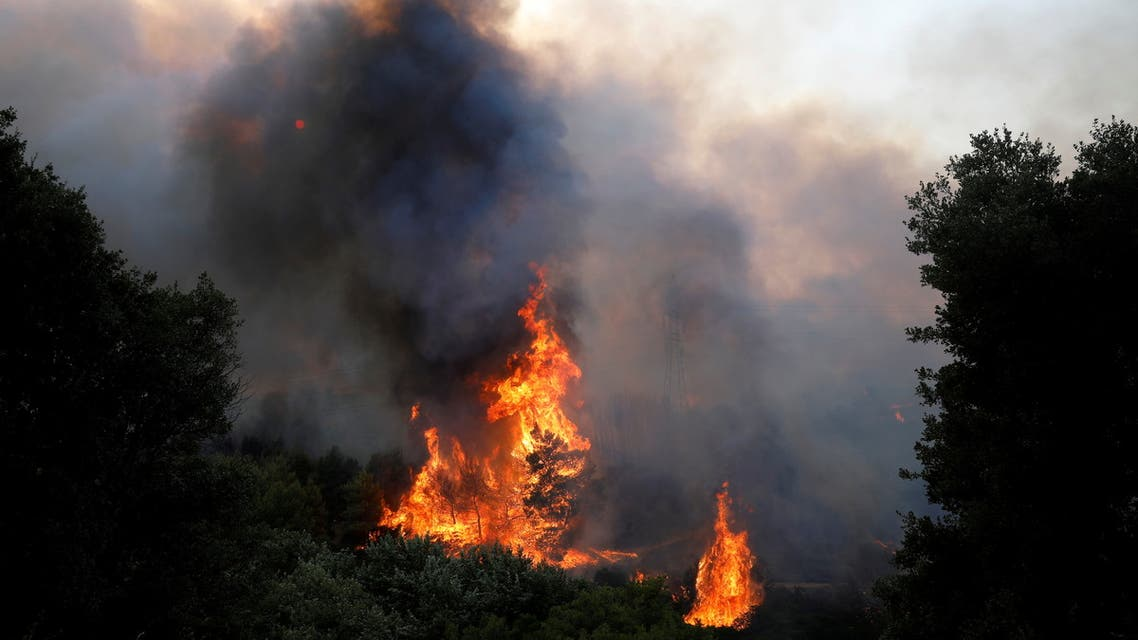 Smoke rises from a wildfire at Varympompi suburb north of Athens, Greece, August 3, 2021. (Reuters)