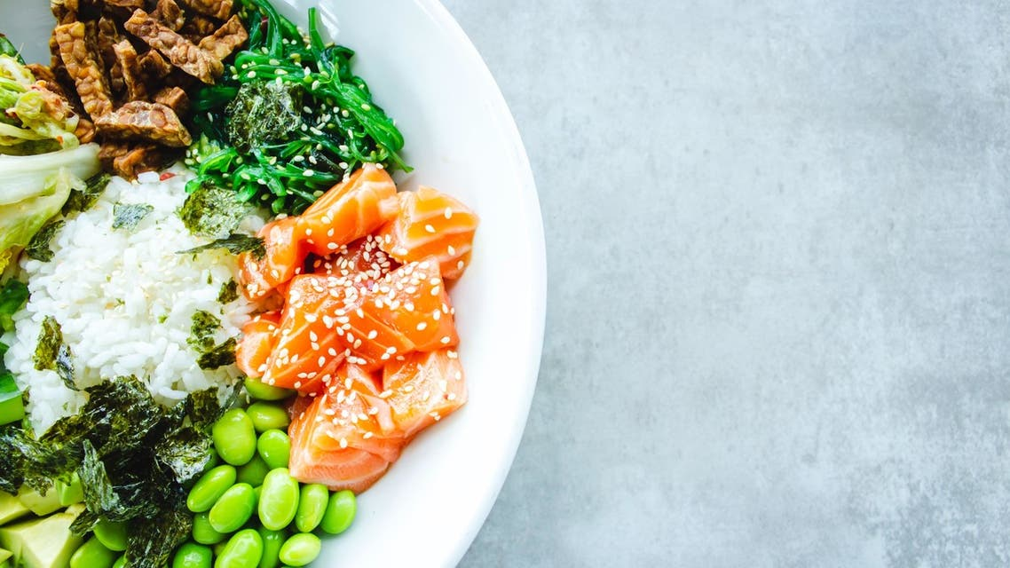 A salad bowl with edamame and raw salmon pieces is pictured. (Unsplash, Louis Hansel Restaurant Photographer)