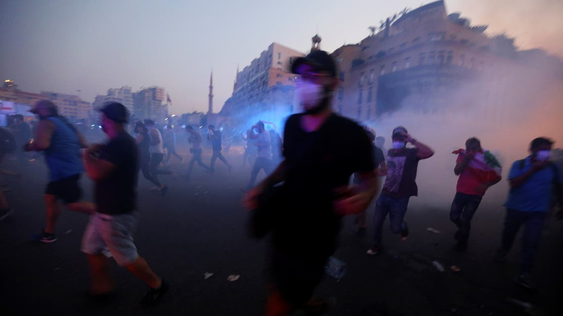 Demonstrators run during clashes with security forces during a protest near parliament, as Lebanon marks the one-year anniversary of the explosion in Beirut, Lebanon August 4, 2021. (Reuters)