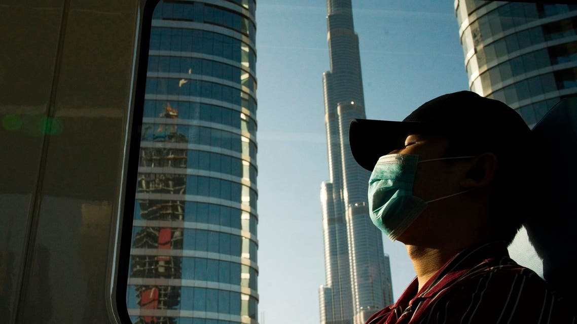 FILE - In this April 26, 2020 file photo, a commuter wearing a face mask to help curb the spread of the coronavirus, sleeps aboard the driverless Metro as it passes the Burj Khalifa, the world's tallest building, in Dubai, United Arab Emirates. After opening itself for New Year's revelers, Dubai now find itself blamed by countries for spreading the coronavirus abroad. That's as questions swirl about the city-state's ability to handle reported cases spiking to record levels. (File phoTo: AP)
