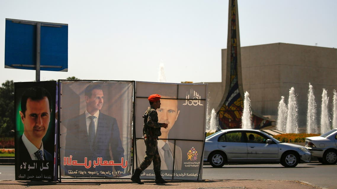 A Syrian military police officer walks past posters depicting Syria's President Bashar al-Assad, during the country's presidential elections in Damascus, Syria, May 26, 2021. (Reuters)