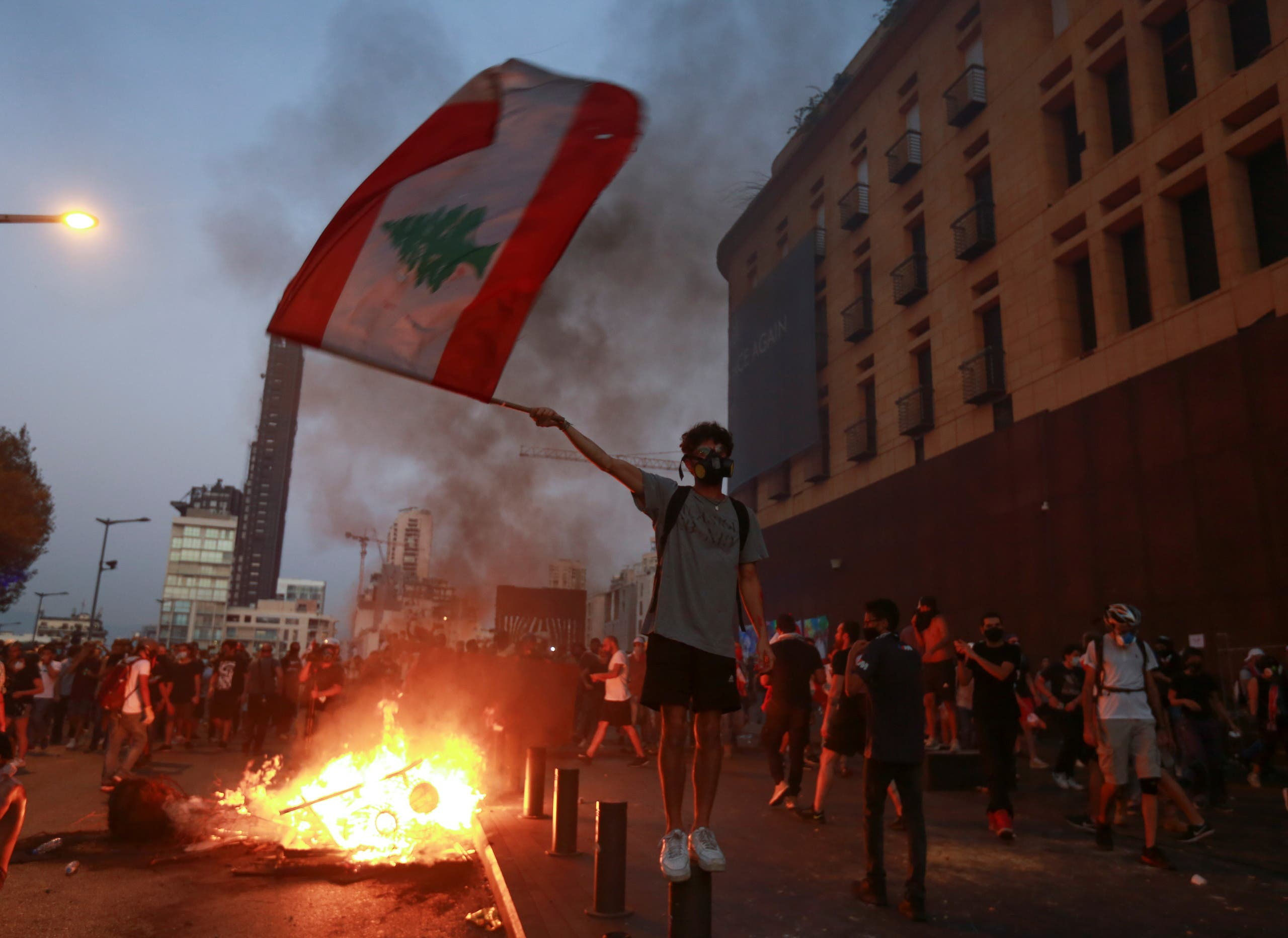 Demonstrators walk near a burning fire during a protest near parliament, as Lebanon marks the one-year anniversary of the explosion in Beirut, Lebanon August 4, 2021. (Reuters)