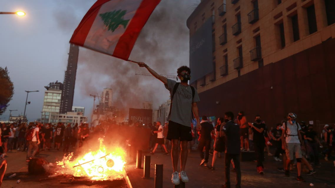 Demonstrators walk near a burning fire during a protest near parliament, as Lebanon marks the one-year anniversary of the explosion in Beirut, Lebanon August 4, 2021. REUTERS/Mohamed Azakir